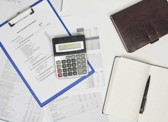 Κομπιουτεράκι, σημειωματάριο και διάφορα χαρτιά που αφορούν οικονομικά μεγέθη εξαγωγών