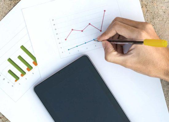 Ανδρικό χέρι κρατάει σημειώσεις σε χαρτιά που απεικονίζουν διάφορα διαγράμματα